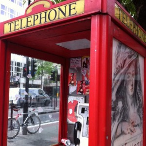 Telephone booth with official advertisment (outside) and unofficial ads and transactions (inside)
